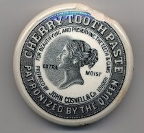 "Image of Box, Toothpaste - White ceramic toothpaste jar lid. The top of the lid has black and white image of the Queen's head and a ring around the lid with numerous small black dots. Printed in white with black shadowing within the ring is ""Cherry Toothpaste Patronized By The Queen"". Printed in black around the head is ""For Beautifying And Preserving The Teeth & Gums"", ""Prepared By John Cosnell & Co London"" and ""Extra Moist""."