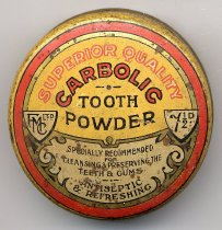 "Image of Box, Toothpaste - Round yellow medicine tin with the remains of powder inside. The lid has a red ring around the edge with a gold ring inside, a beige and gold motif and 2 beige shields. Printed on the yellow area is ""Superior Quality Carbolic Tooth Powder"" in a mix of beige, red and black.  