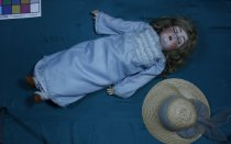 """Image of Doll - Large female child bisque head doll with composition body wearing pale blue dress and straw hat. Was named Victoria by owner.   Doll has mouse brown (real?) hair that falls just past shoulder length.  The hair sewn onto fabric that is then glued to head (a repair?). The moveable blue eyes are sleeping eyes - opens when standing closed when lying down. Eyelashes are attached to the eyes and are also painted on the face. Eyebrows are painted on the face. Doll has open mouth with four upper teeth showing, lips are painted orange with dimple in chin, pale complexion with rosy cheeks.  Marking on back of head """"K Star R Simon & Halbig 403"""" so made by Kammer & Reinhard between 1920 and 1932 ( see notes) . The K star R are hidden under the repair but can be faintly seen if the repair is gently lifted. Head is bisque.  The body is composition with ball joints at shoulder, elbow and wrist on the arms and at hip only on the legs.  Doll wears light blue nylon? long sleeved dress. Dress has synthetic frill and lace across the bodice and falls straight to feet with synthetic frill at hem. Dress has rough hand stitching and machine overlocking and looks as if a baby's dress has been reworked to fit the doll. Doll also wear matching blue petticoat from waist to feet made in the same way with lace at the hem and also matching blue bloomers to the knee. Doll also wears a white cotton shift that may be original - hand sewing very neat. Doll wears white nylon honeycomb pattern socks to the knee and brown vinyl tie on shoes. Large straw hat has pale blue chiffon scarf round centre.   Note found with doll """"Victoria c 1900 purchased 1976"""" Date may not be accurate."""