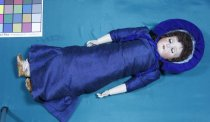 Image of Doll - Large female child bisque head doll with composition body wearing dark blue silk dress and dark blue velvet bonnet.