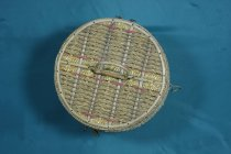 Image of Basket, Needlework - Round cane sewing basket with padded and quilted pale green interior. The lid and sides of the basket have two different types of weave - the main one which forms wide stripes covering most of the basket is a coarser style which a plait alternating with a twisted string,  The other weave is a finer more golden coloured material and forms the central stripe under the handle on the lid and also the edges of the lid and of the sides. The two weaves are seperated by a band of red cane. 