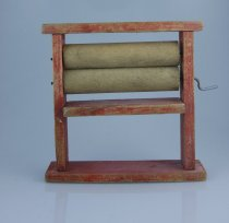 Image of Toy, Washing - Wooden toy wringer washing devise, with two natural wood rooler and red stand and has a metal pin to turn the rollers. Red in colour but worn and faded.