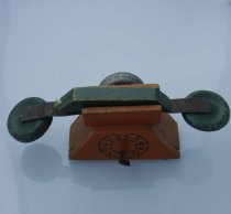 Image of Toy, Telephone - This toy telephone is in two parts. The receiver which is dark green in colour, wooden hand piece attached to a metal strip that has a round metal disc on each end.
