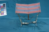 """Image of Chair, Folding - Small folding chair with red and blue striped canvas seat. Legs are made from stainless steel tubing and opens outs so that the struts form as cross with reinforced section in the middle. Brace across the bottom can be adjusted and supports up the side are made from blue and white striped canvas.  """"PMcAuley"""" is hand written on the underneath of the canvas."""