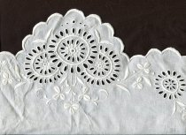 Image of Cover, Bolster - White cotton bolster cover with broderie anglais embroidery at the ends.  Cover is joined with flat fell seam.  The embroidery at each open end is a hand worked floral broderie anglais design with scalopped edge. This is on the top - the under part is scalopped but has no embroidery.