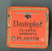 "Image of Tin, Medicine - Orange tin with removable lid. On the lid is ""Elastoplast Elastic adhesive Plaster "" in black. on the side is same with ""British Made 1 in wide 5-6 yards when stretched"" and "" made in England by T J Smith and Nephew Ltd London Hull Manchester and Glasgow."""