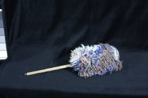 Image of Duster - Multicoloured wool duster with wooden dowel handle.  Wool attached around the top in colours that include blue, pink, white grey and red.  Small metal loop at the end of the handle so that it can be hung up.