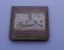 "Image of Mirror, Hand - Small ""1940 NZ Centennial"" souvenir hand mirror in plastic envelope/pouch with mock wood grain finish. In the centre of the cover is transfer image in brown of the buildings where the centennial was held. Mirror is under the flap."