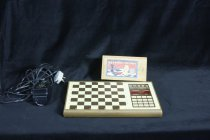 Image of Chess - Electronic Chess set compromises board, small box with pieces and electric cord.