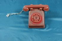 Image of Toy, Telephone - Red plastic toy telephone. Phone has dial at the front but the numbers are now missing and dial does not turn well. Behind the dial is a bell which rings when the dial is turned. Has lift up handset which is attached with string ( although this may be a repair)