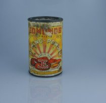 """Image of Tin, Food - Round tin with paper label for """"Edmonds Baking Powder"""". Label is orange and yellow radiating stripes like the rays of the sun with """"Edmonds"""" in red, """"established prize 1879"""" in black and """"Baking powder"""" in white with black outline. Below that is """"sure to rise"""" and a large red """"E"""" which is the logo with drawings of cakes etc.  On the back is Directions for use and a recipe for scones, """"prepared with cream of tartar manufactured by T J Edmonds 375 Ferry Road Christchurch NZ 14 oz net"""". Down the side are two scrolls with """"Public opinion once used always used try it"""" and """"Makes light pastry, scones, bread, tea cake puddings"""""""