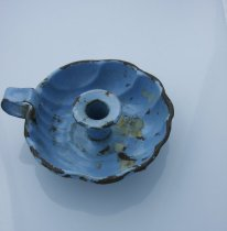 Image of Candlestick - Blue enamel candle holder.  Holder is scalloped dish shape which is quite deep.  In the centre is a raised circle in which to place and secure the candle.  To the side is a loop of metal which acts as a handle.  Some wax from previous candles inside.
