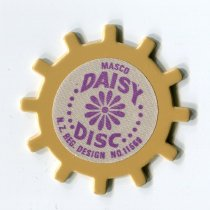 "Image of Loom, Lace - Small round plastic disc called a ""Daisy Disc' or ""Daisy Wheel"" .  The wheel has evenly spaced knobs around the edge.  In the centre printed in purple is ""Masco Daisy Disc NZ design No 11558"". Wool is wound around these knobs and tied off and the wool slipped off the knobs so that daisy pattern in wool remains and can used as decoration or several sewn together to make something. Sheet of typed instructions included."