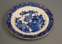 """Image of Plate - Royal Worcester transfer-printed side plate for tea cup and saucer  955/37.2 and .3 with blue on white Willow pattern.  The design features willow trees, pagoda-like buildings, and a bridge with figures standing on it. The rim is decorated with gold. On base has a blue stamp """"V389"""""""
