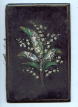 "Image of Blotter - Book-style blotter with a black lacquer cover.  Spray of lily of the valley flowers painted on front, inset with paua(?) shell.  Inside lined with blue and white paper, encloses pink blotting paper.  Inside at the front ""E.H. Morgan Jan 19/8"" (1908?) is written in pencil.  Written below that in blue pen is ""Miss E.L. Morgan"" (by Museum?).  ""Won at the Festival by E. Morgan"" is written in pencil inside at the back."