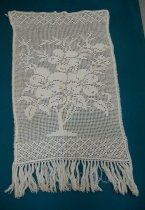 Image of Antimacassar - Rectangular white cotton crocheted antimacassar.  Centre design of  roses with foliage in a vase.  Criss cross pattern at top and  bottom.  Edged with fringe at bottom.