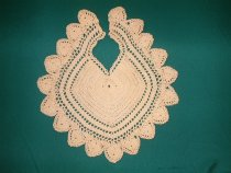 Image of Bib - Babies cream cotton crocheted bib. Diamond pattern neckline. Crocheted middle with 3 rows of eyelet work, outside scalloped edge. Indications of ties at back.