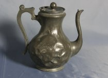 """Image of Coffeepot - Pewter Coffee pot salvaged from the Elginshire. Has round finial on hinged lid. Body narrows below lid then widening out towards the base which has been dented in several places. Long upright spout from bottom of the bowl is curved close to the body. The angular handle with curved thumb rest at the top has holes for cooling across the top and down the side.  Has """"Elginshire"""" engraved on one side of the body.  On base has """"3245"""" in double circle and """"patent handle """" around the edge. Also """"1075""""? and other numbers.  dented bowl, patent handle"""