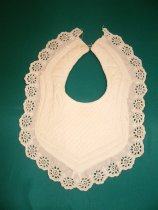 Image of Bib - Babies white quilted bib. Broderie anglaise lace with scolloped edge trim.  Various designs on quilting from diamond to scrolled.  Turned tape edging quilted area. Button on left side and large loop on right side at neck.   Front and back both the same.