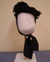 Image of Bonnet - Black straw bonnet, no brim as such but shaped (upturned at the front), black lace trim around upturned edge and feathers on back of the crown.  A wide grosgrain ribbon tie in a loop ties under chin in big bow