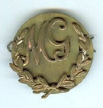 """Image of Badge, Military - Brass badge with """"M.G."""" between a wreath and mounted on a back.  Badge is in three parts. top is separate """"MG"""" section with two loops at the back. Middle section is brass disc with the wreath attached and which also has two loops at the back. It also has two holes through which the """"MG"""" loops go through so that the third part - the brass pin - goes through all four loops securing it altogether.  MG possibly stands for machine gun (http://www.diggerhistory.info/pages-asstd/abbreviations.htm)"""