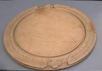 Image of Board, Cutting - Round wooden bread board, carved edge like simple wreath with a flower at each side