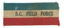 Image of Badge - Coloured ribbon with a blue stripe along the top, a white stripe in the middle and a red stripe along the bottom. Has `SC Field Force' printed in black on white stripe.  The first type of badge sold in Timaru in 1914 for raising War funds. Sold at 2/6 each.
