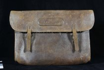 """Image of Bag - Satchel, leather, light brown, rectangle shape.   Bag opens at the top. On the front in the middle centre of the lid is the inscription """"T N Brodrick"""". Bag is sealed closed with two leather straps on the lid and metal buckles on the main part of the bag.   On the inside of the lid is a shorter leather flap with holes, which attach into the bag with six metal rings. On the right is a leather strap with a metal dome at the end. This strap loops though the metal rings, fastening the shorter flap of the bag shut.   Attached to the back of the bag is the shoulder strap, which has a metal buckle."""