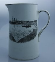 Image of Jug - White jug with black lettering 'Thomsons Xmas Good Wishes' on one side and black and white image of the Timaru harbour on the other side.  Three stems of a floral  design lie behind the words.  The coastal scene  is viewed through two rocks (Dashing Rocks?) across water to harbour with steam and sail ships and buildings of the town behind.  
