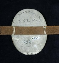 "Image of Armband - Leather armband with ""T.V.R.B."" above an anchor, painted on oval leather patch on leather strap with buckle.  White background, red border, blue anchor with brown rope.  Lettering is blue highlight with red.  Handwritten on back in black, ""Timaru Volunteer Rocket Brigade /' C. G. Vogeler / 1882""."