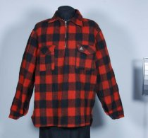 """Image of Jacket - Red and black checked woollen bush shirt.  Front: Round neck with collar, stiffened and backed with black cotton. Centre front opening 22cm metal zip to chest level.  Patch pockets each side with flaps backed with black cotton. Flaps button down with black button and machined buttonhole. Left pocket has triangular label """"Egmont"""" with mountain logo. Bottom of jacket rounded up at the sides.  Back: Plain. Bottom rounded up at sides.  Sleeves: Long sleeves with opening at wrist and cuff backed with black cotton and buttoned with black button and machined button hole.  Construction: Machine made. Seams overlocked. Hem overlocked.  Label:"""" Egmont Showerproofed Wanganui Woollen Mills Ltd Made in New Zealand Handwash or Dryclean Do not rub 100% Pure New Wool  XL """" Wool mark and mountain logo."""