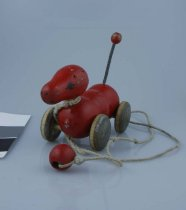 Image of Toy, Pull - Small red wooden pull along dog at least 40 years old. Plain wooden wheels and coiled wire tail with red wooden knob at the end. String attached at the front.