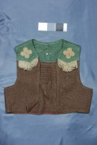Image of Costume - Child's cowboy costume made from a green and brown Hessian with leather trim.  Waistcoat: Front: Front opening V neckline and points at the hem. Green Hessian yoke with pale brown leather fringe and four petalled flower appliqued on with stud in the middle. Brown Hessian jacket. Back: Green Hessian yoke fringed at bottom. Leather bull's head appliqued centre back with two chrome studs for eyes. Brown Hessian jacket with leather star appliqued and with central stud.  Chaps (Leggings): Front: Brown Hessian waistband with leather bullhead appliqued centre font and eye studs. Band has leather strap and buckle. Two large button holes in band - ? Elastic at waist inside. Chaps in green and brown Hessian have leather clover leaf like appliques with centre stud - three on each leg. Side of chaps fringed on outside edge. Back: Leather straps at back of thigh to attach. Chap legs joined near bottom.  Construction. Overlocked seams and hems and double top stitched. Machine sewn. Probably home made.