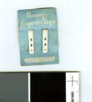 "Image of Sewing Supplies - Small white metal clasps on pale blue cardboard with ""Newey's Lingerie Clasps"" in white and also ""Made in England by Newey Bros Ltd"""