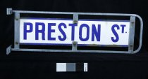 """Image of Sign, Street - Small street sign with """"Preston St """" enamelled in dark blue onto white enamelled surface in capital letters on both sides. This panel is screwed onto a metal frame with rounded ends. There is a gap between the enamel panel and the metal frame. Metal frame has ends to attached to pole with holes for screws to go through."""