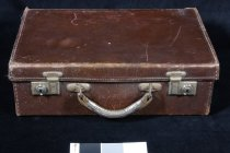 "Image of Suitcase - Small brown leather suitcase.  Has leather handle and two metal clasp ( rusty).  Inside is lined with pale blue canvas andf has handwriiten on the inside lid "" J L Laurenson 443188 King St Temuka N.Z."""