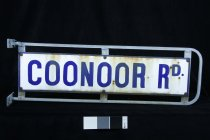 """Image of Sign, Street - Small street sign with """"Conoor Road """" enamelled in dark blue onto white enamelled surface in capital letters on both sides.  This panel is screwed onto a metal frame with rounded ends.  There is a gap between the enamel panel nd the metal frame.  Metal frame has ends to attached to pole with holes for screws to go through."""