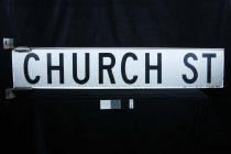 "Image of Sign, Street - Large street sign with ""Church Street"" in computer cut lettering? glued on to metal (aluminium  based?) panel.  The black lettering is in capitals  on both sides.  Attached to the ends are sections to screw into the pole."