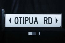 "Image of Sign, Street - Large street sign with ""Otipua Road"" in computer cut lettering? glued on to metal (aluminium  based?) panel.  The black lettering is in capitals  on both sides.  Attached to the ends are sections to screw into the pole."