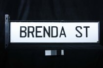 "Image of Sign, Street - Large street sign with ""Brenda Street"" in computer cut lettering? glued on to metal (aluminium  based?) panel.  The black lettering is in capitals  on both sides.  Attached to the ends are sections to screw into the pole."
