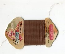 "Image of Thread - Cardboard with nylon thread wrapped around. Shaped cardboard has coloured picture of a woman in pink dress / dressing gown and the words ""Glista Nylon mending"". In the middle is the fine wrapped nylon thread with plastic wrapper over it. At the base of the card is ""Unsurpassed for all superfine hose Use single strand for fine mending and four strands for heavy mending British Made."""
