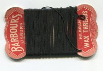 "Image of Thread - Cardboard with black linen thread wrapped around. Shaped red coloured cardboard has the words ""Barbour's Lisburn N Ireland Hilbran wax threads"" in white.  In the middle is the thick black linen thread.   On the back is handwritten ""Adie"" twice."