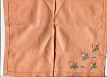 Image of Napkin - Orange linen embroidered table napkin. Napkin is drawn thread embroidered hem stitched.  In one corner there are four hand embroidered flowers in coral coloured buttonhole stitch for flowers and green satin stitch for leaves.