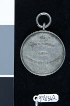 """Image of Medal, Military - New Zealand Long and Efficient Service Medal awarded to Serg. J. D. Robertson awarded for 16 years service in 1908.  Obverse:  A picture of a crown surrounded by a wreath.  There are stars at the top and sides of the crown.  Below the crown are  the initials N.Z., a ribbon bow, and the initials G.T. White.  Reverse:  Reads """"FOR LONG AND EFFICIENT SERVICE""""  The edge of the medal reads """"NO.416 SERG.J.D.ROBERTSON.TIMARU CITY RIFLE VOLS.(1908)"""".  A Metal loop would have attached the ribbon to the medal.  No ribbon is present."""