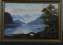 Image of Painting - Oil painting of Lake Manupouri. Painting depicts Lake Manapouri with scrub and trees in the foreground and a view to tree covered hills and mountain in the distance. Sun blushed sky.