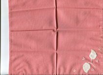 Image of Napkin - A pair of pink linen appliqued and embroidered table napkins.  Napkins have a narrow hem slip stitched. In one corner there is a sprig of leaves - two leaves appliqued white cotton with chain stitch stem. Five little motifs in lazy stitch surround the main image.