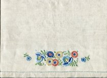 Image of Mat, Table - Pair of hand embroidered table mats.  Mats are oblong shaped in cream linen and have drawn thread embroidered hemstitching in blue around the four sides. At the centre front is embroidered a floral design with blue, orange and yellow flowers in buttonhole, satin and chain stitches and with green leaves and stems in lazy daisy and stem stitches.