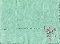 Image of Runner, Table - Green linen table runner with pink embroidery. Matched 2012/107.14  Runner has drawn thread embroidered hemstitching around the outside edge and then again 8cm in from the edge.In each corner is floral motif hand embroidered in two tones of pink thread for the flowers and some leaves and green thread for stems and other leaves.Stitches used are satin, lazy daisy and stem.Two of the motifs feature two flowers and the other two have three flowers and three fruits.