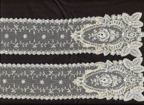 Image of Collar - Lace collar which could be a collar or lapets. Cream needlerun styled lace with fine net ground and floral motifs and edging. Machine made.  At each end there is a medallion piece which has been stitched to the length of lace with thread which has discoloured thus showing the outline of where it is attached.