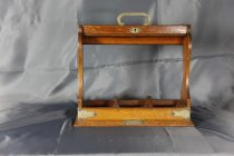 Image of Tantalus - Small wooden oak tray to hold three bottle which are missing. Tray base has square compartments for three bottles. Sides are shaped at the narrower ends but with the longer sides open so that any bottles would be visible and with a wooden top which can be locked so that bottles would not be able to be removed.